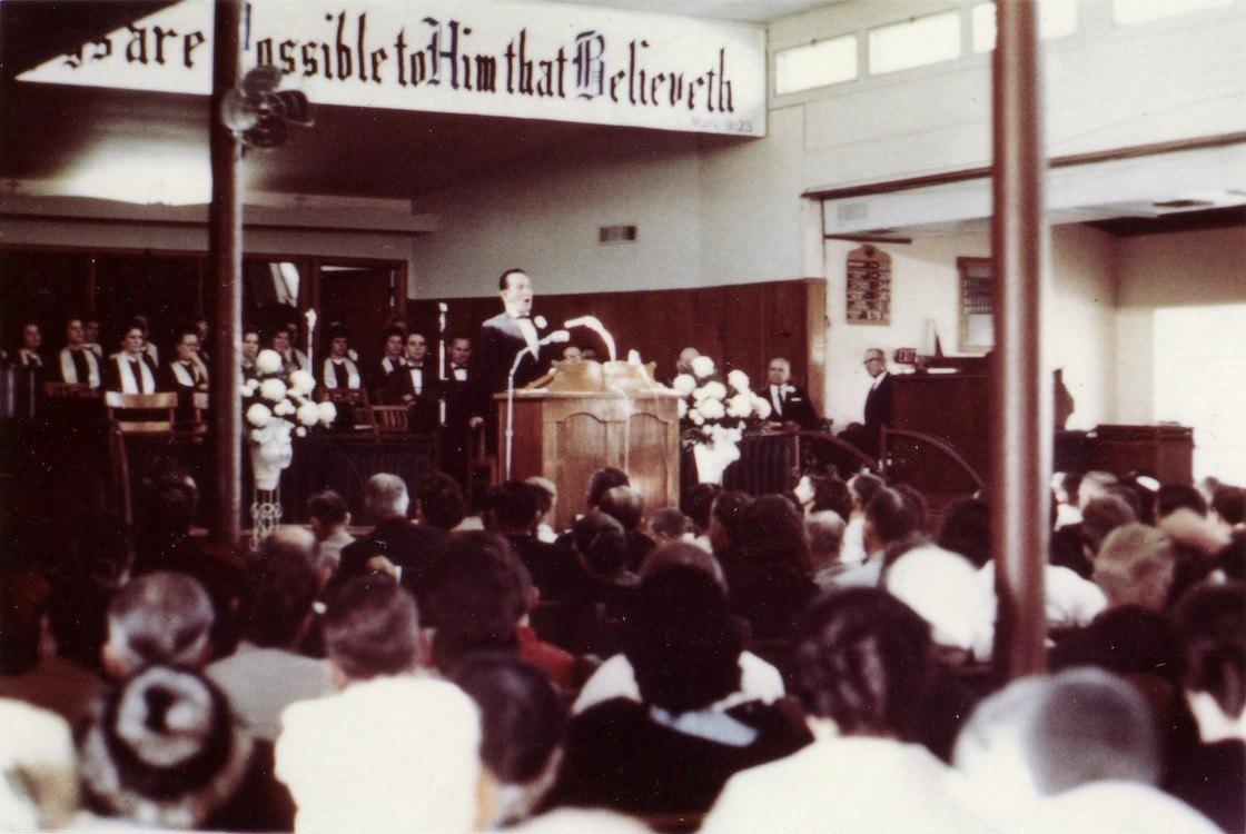 Morris Ungrun zingt in de Life Tabernacle in Shreveport, Louisiana. Op de foto zit William Branham rechts van hem, naast de bloemen