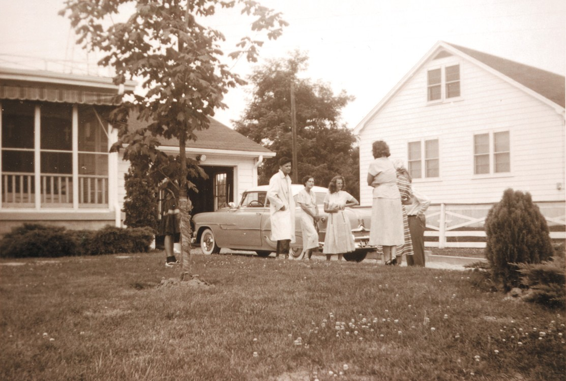 William Branham bij de garage van zijn thuis in 1954. Terwijl hij de auto wast, komen er bezoekers langs die een gesprek met hem beginnen. Rechts is het huis van de familie May.